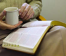 Word in Time image - person reading the Bible with mug of coffee