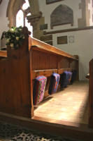 Sunlit pew and kneeling pads