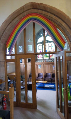 A photograph of the outside door of the creche. This includes a rainbox above the door and the word creche. It is possible to see inside where there is seating for adults, rugs for children to play