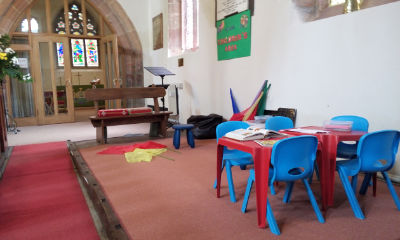 A photograph of our childrens area including tables and chairs, books and colouring, space on the floor to move around, seats for adults and flags for worship.