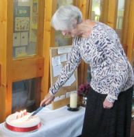 Elaine cuts the 110th anniversary cake