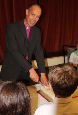 Bishop Richard, the Bishop of Kingston cuts the cake