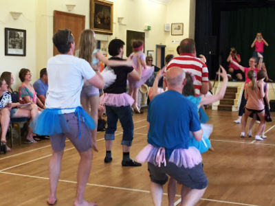 Dads and kids doing ballet in the hall