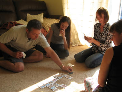 family playing Bible card games on the carpet