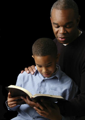 father and son read Bible together