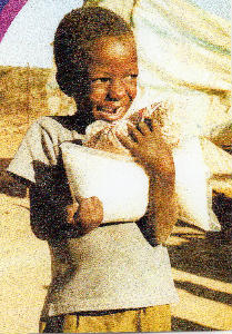 Boy with bag of grain and huge smile