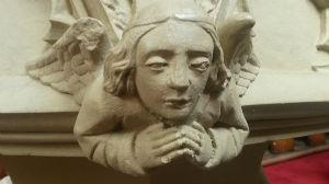 Stone angel on baptismal font