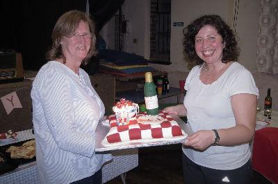 Sue presents Cristina's surprise birthday cake.
