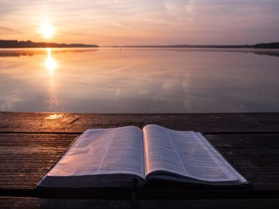 Open bible by water