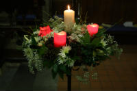 Advent crown showing three red candles and one white candle surrounded by greenery