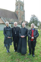 Revd La, Bishop Oliver, Fr Guy and Fr Peter stood outside the annexe side of church in the graveyard