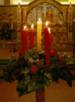 four red and one white advent candles surrounded by greenery and red baubles