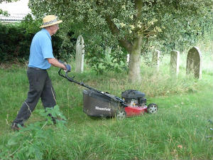 Fred mowing the grass path between headstones