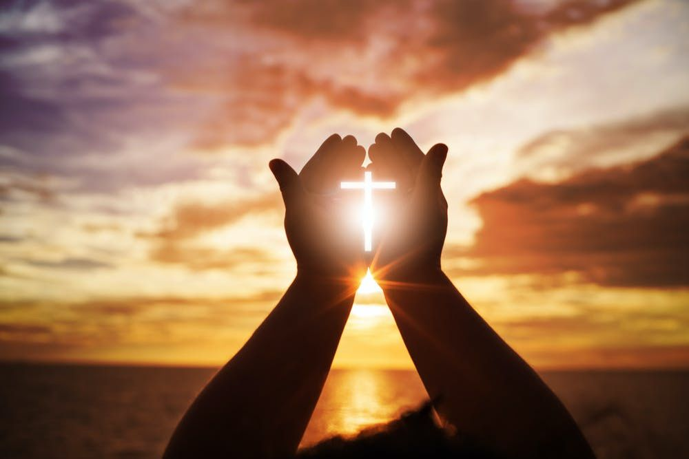 Hands raised in front of rising sun with image of a cross between them