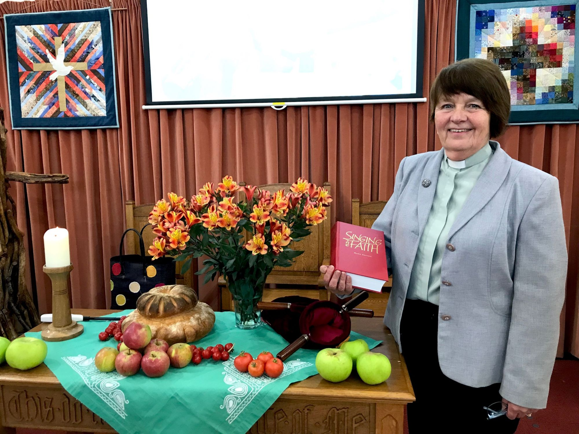 Revd Maree Farrimond with the New Hymn Book at the Harvest Table