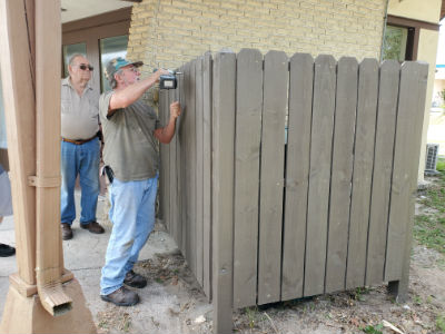 Fixing the fence around the garbage cans
