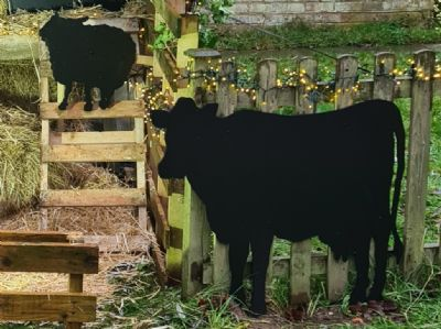 Black cut out cow and sheep against a wooden fence and ladder with straw