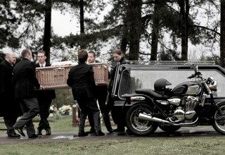 A coffin being unloaded respectfully from a hearse