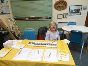 lady sitting behind welcome table