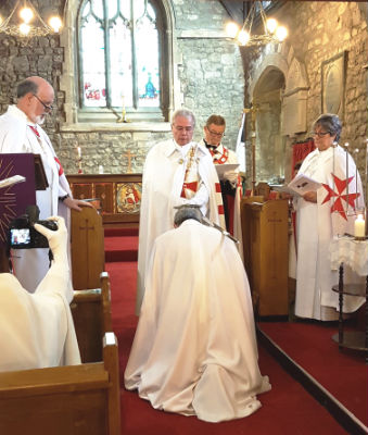 The new knight kneels to receive the accolade