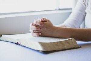 Hands prayerfully held over Bible