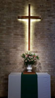 flower arrangement under a lit cross