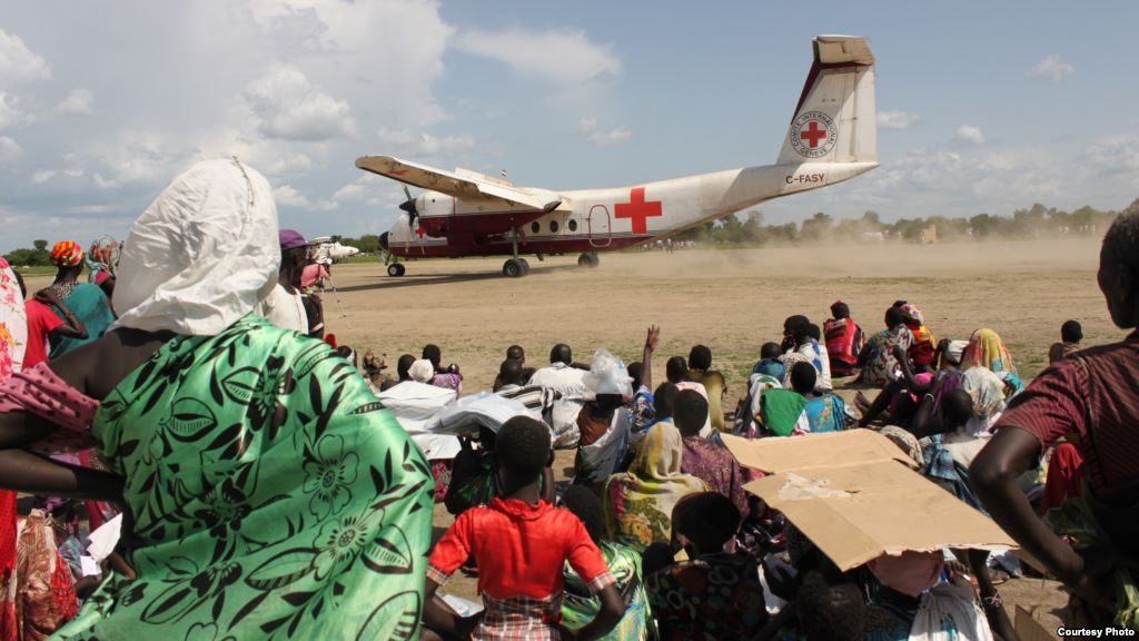Red Cross plane arriving - people waiting