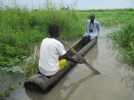 flooded land with two people on wooden log shaped boat