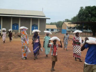 ladies carrying sacks of food away on their heads