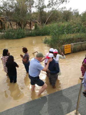 Dave P uses the waters of the River Jordan to bless pilgrims from Malaysia.  Photo taken during Holy Land Pilgrimage 29th Nov 2018