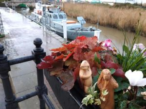 Mary and Joseph figures in flower pot next to small canal