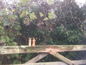 Mary and jospeh figures on a wooden gate with leaves behind them