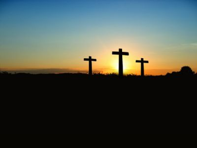 Three crosses with sun set