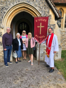 Group standing outside Wyddial Church with St Giles Banner