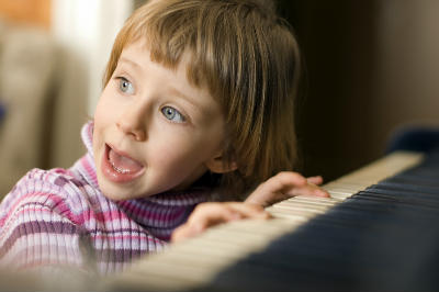girl playing piano and singing christmas carols