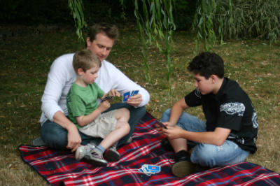 father and sons play Bible games on the rug