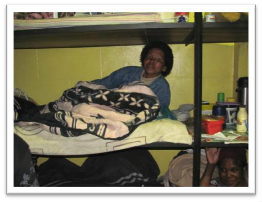 A female shelter user tucked into her bunk