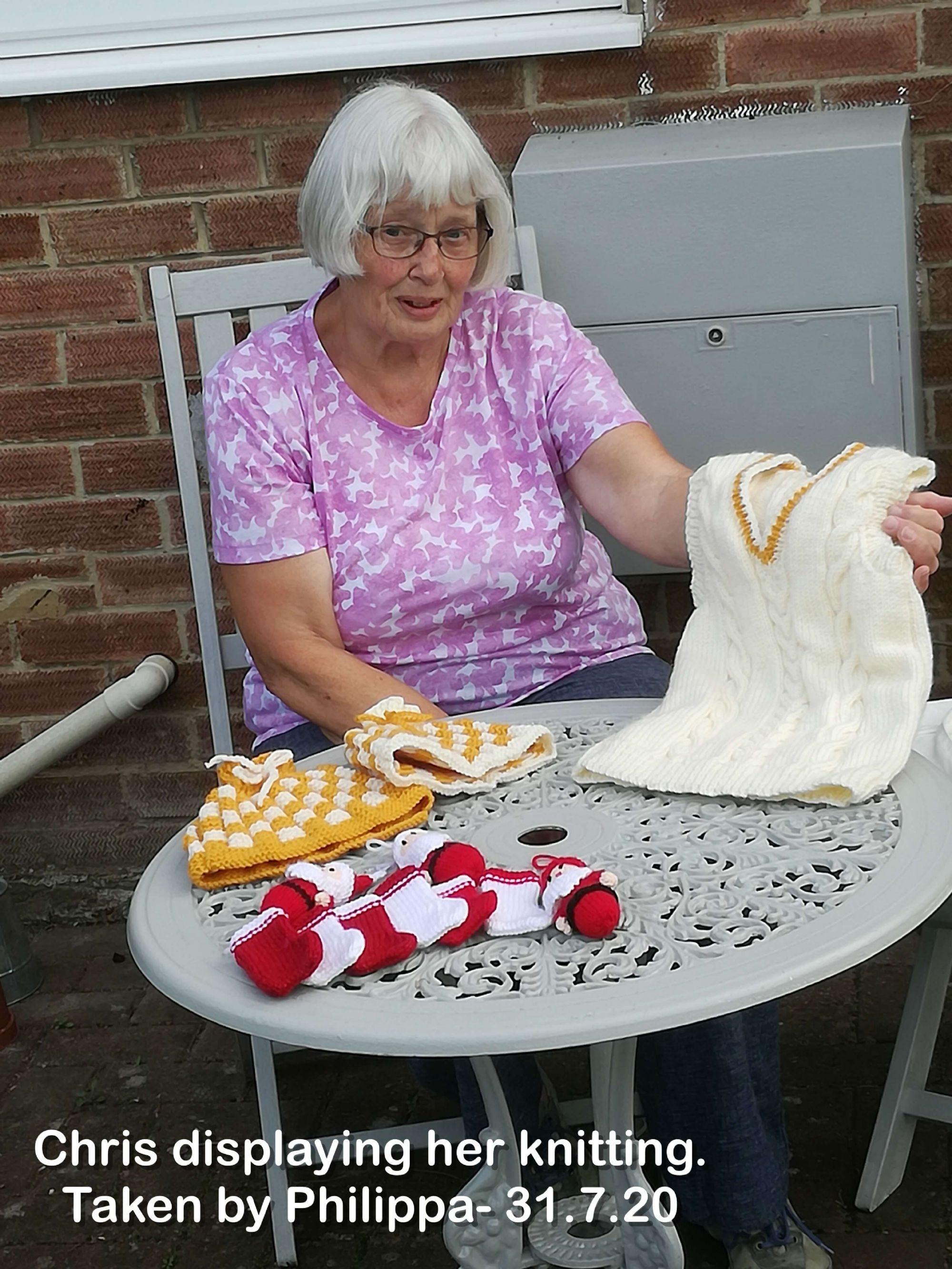Chris displaying her knitting.