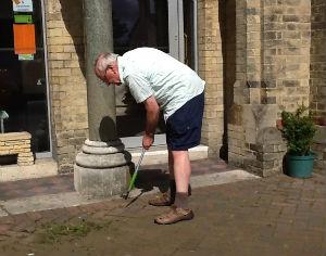 Church Secretary weeding the forecourt