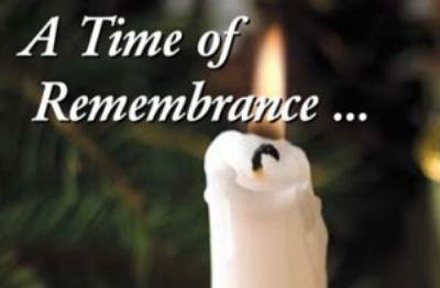 Photo of Candle lit  background green fir trees words say time of rememberance