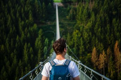 Man walking rope bridge